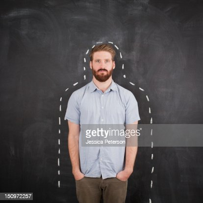 Young man with chalk outline on blackboard, studio shot