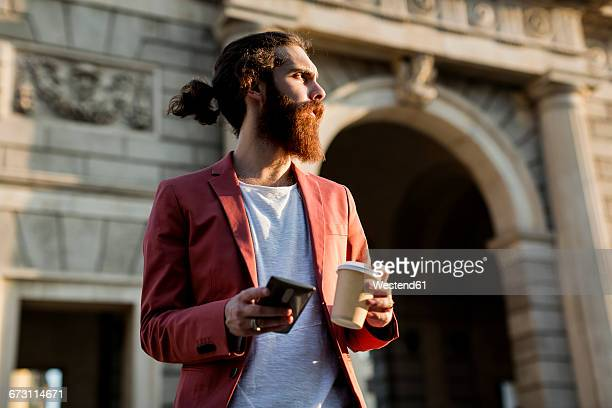 Young man with coffee and smartphone looking at distance