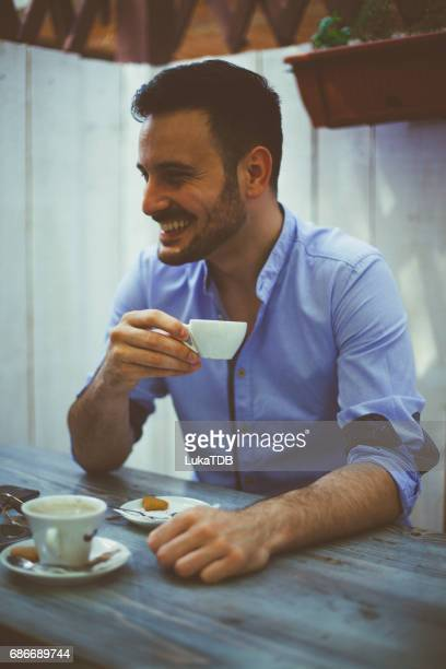 Young man with cup of coffee at the bar