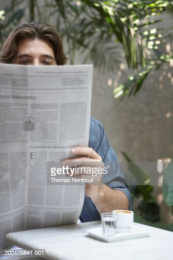 Young man with cup of coffee reading newspaper at outdoor cafe : Stock Photo