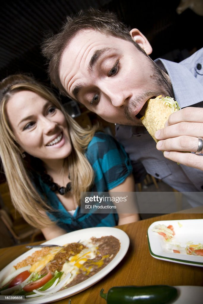 Young Man with Date Eating His Taco at Mexican Restaurant