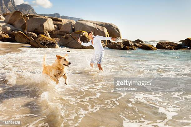 Young man with dog on beach