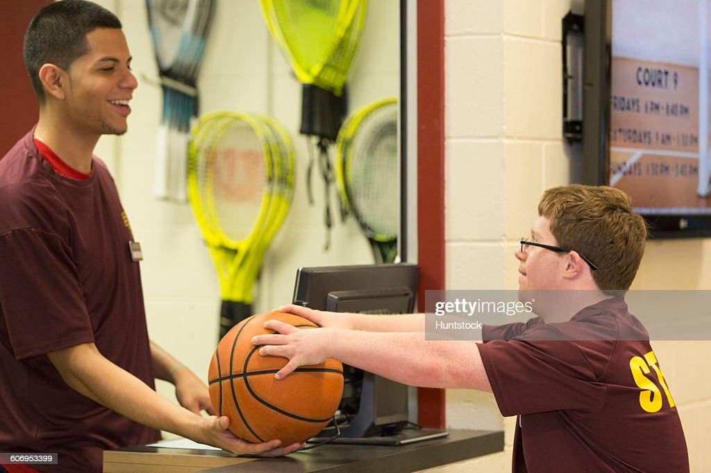 Young man with Down Syndrome holding a basketball with supervisor at college equipment dispensary