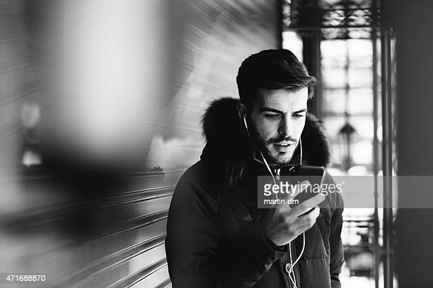 Young man with earphones texting on smartphone