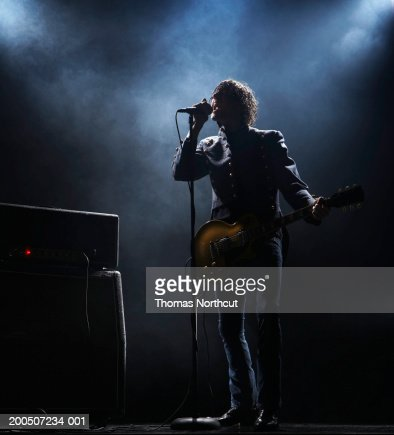Young man with electric guitar singing into microphone on dark stage : Foto de stock