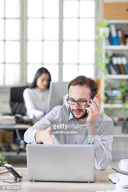 Young man with eyeglasses talking on the phone at workplace
