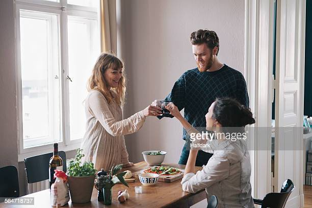Young man with female friends toasting wine at home