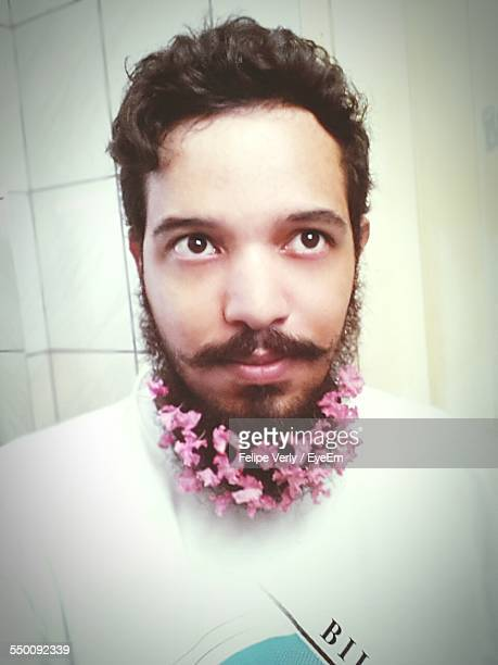 Young Man With Flowers In Beard Looking Away