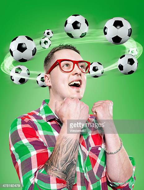 Young man with flying footballs around his head, Composite