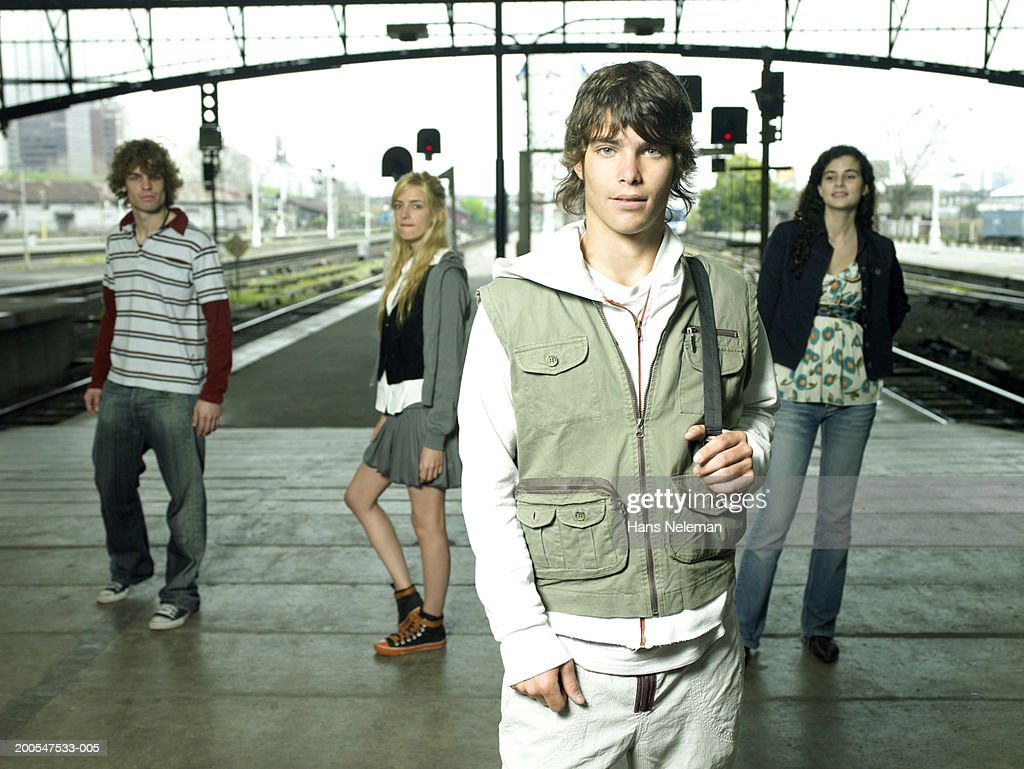 Young man with friends at railway station, posing, three quarter length : Stock Photo