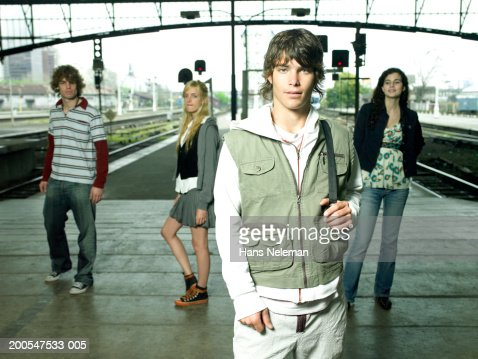 Young man with friends at railway station, posing, three quarter length : Stock-Foto
