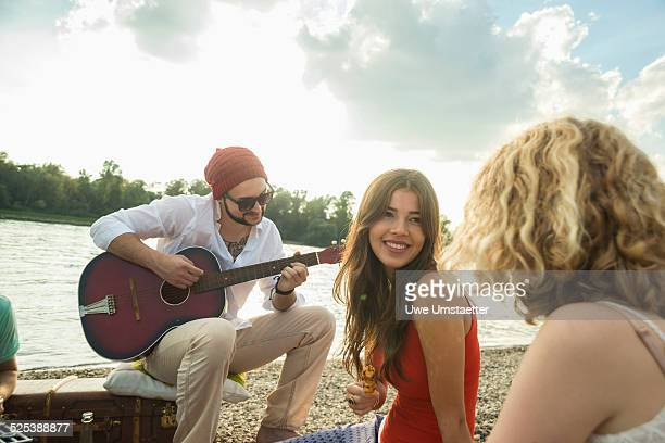 Young man with friends playing guitar