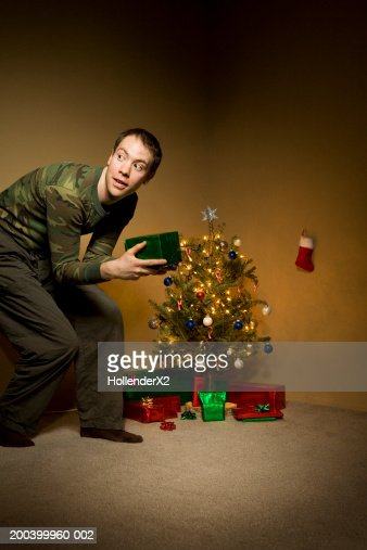 Young man with gift near Christmas tree, looking away