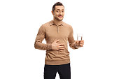 Young man with a glass of water holding his hand on his stomach isolated on white background