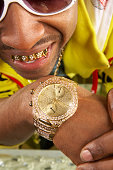 Young man with gold teeth and watch, close-up