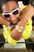 Young man with gold teeth and watches, close-up