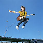 Young man with guitar leaping in air outdoors, low angle view