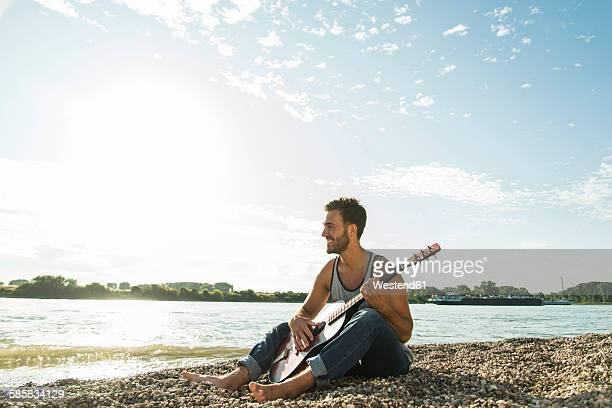 Young man with guitar sitting by the riverside