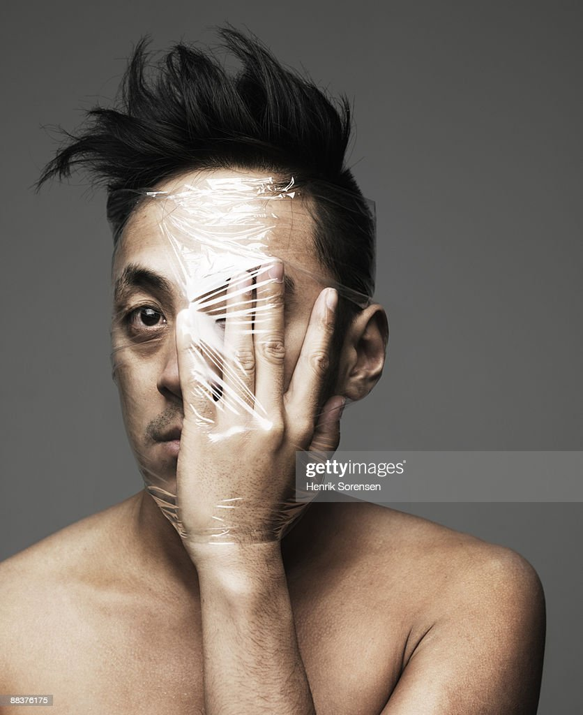 young man with hand  front of his eye wrapped up w : Stock Photo