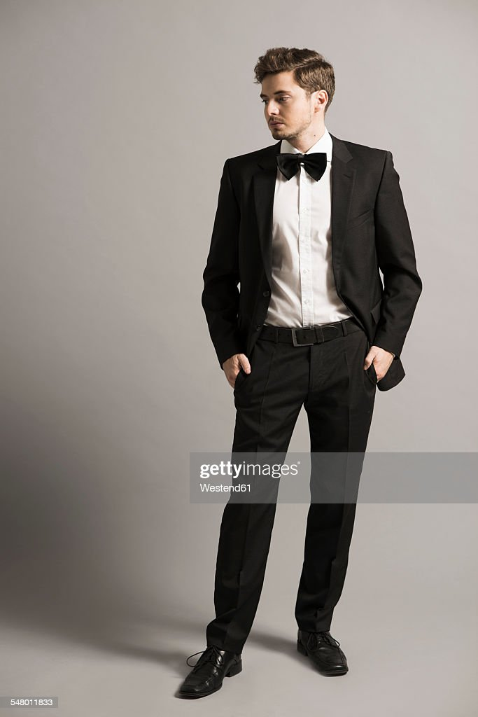 Young man with hands in his pockets wearing black suit, white shirt and bow : Stock-Foto