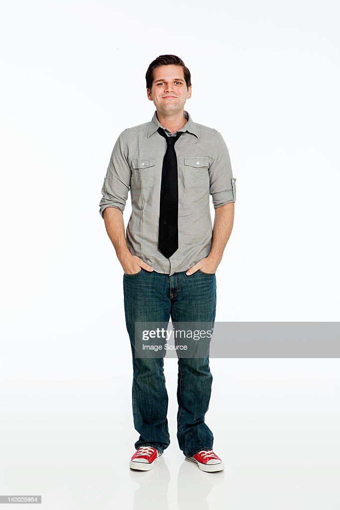 Young man with hands in pockets against white background : Stock Photo