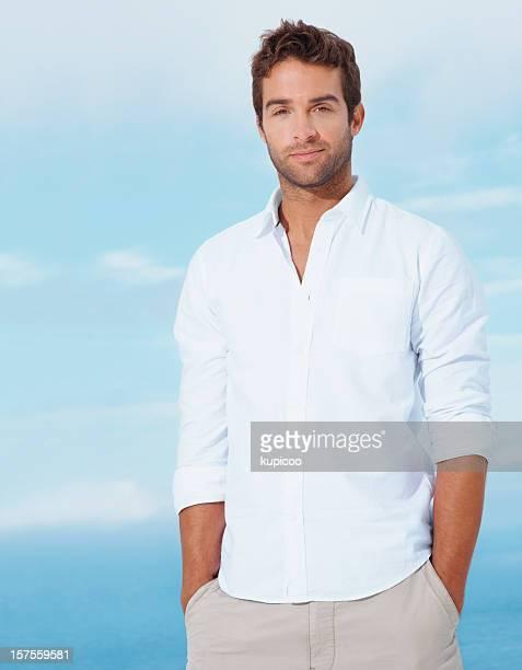 Junger Mann mit Händen in den Taschen stehen vor blauem Himmel