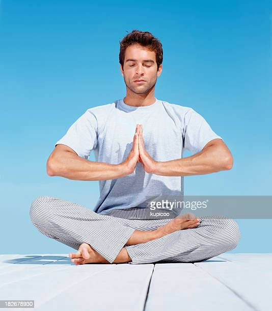 Young man with hands joined meditating on pier