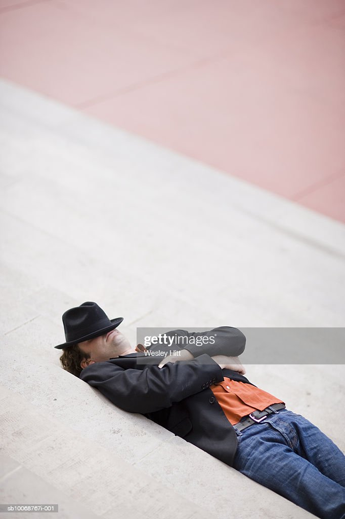 Young man with hat over face, sleeping in street : Stock Photo