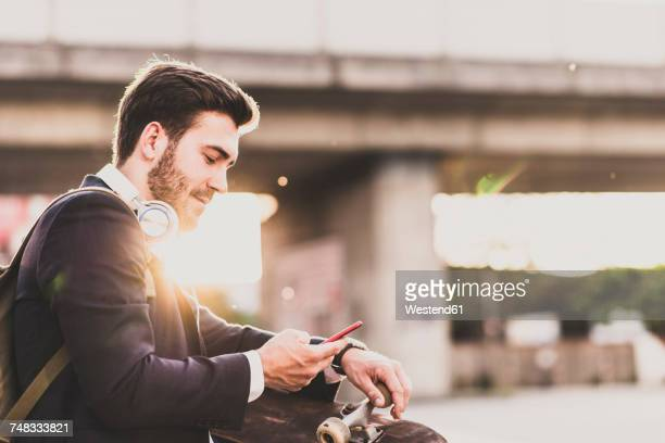 Young man with headphones and skateboard checking cell phone