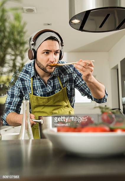 Young man with headphones cooking in kitchen at home