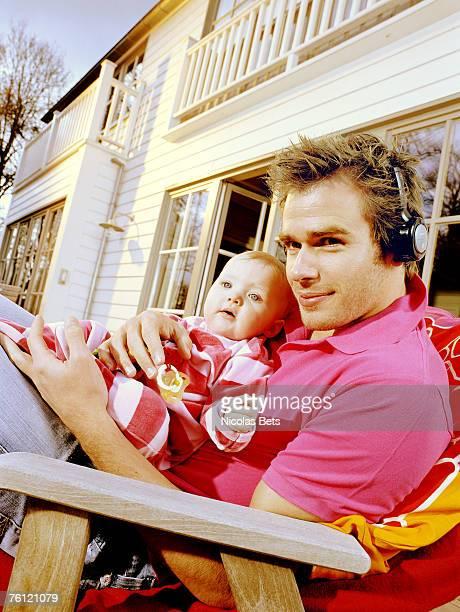 Young man with headphones holding baby, lying on a deck chair