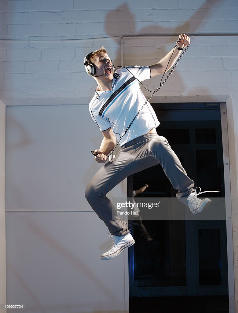 Young man with headphones jumping, laughing