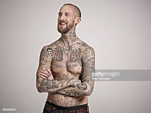 Young man with heavily tattooed body smiling.