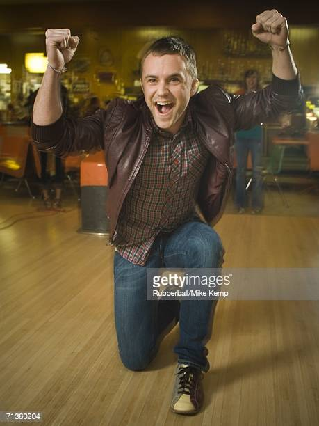 Young man with his arms raised in excitement in a bowling alley