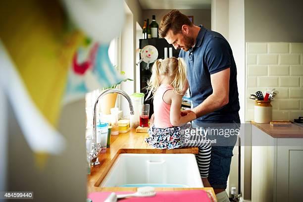 Jovem com sua filha preparar o almoço na cozinha