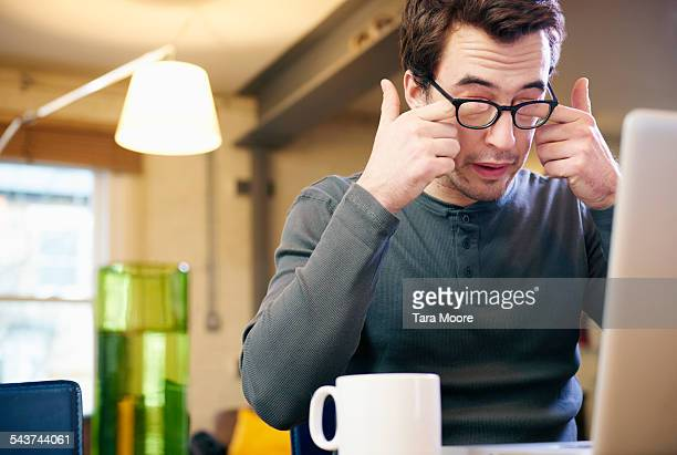 Young man with laptop at home rubbing his eyes