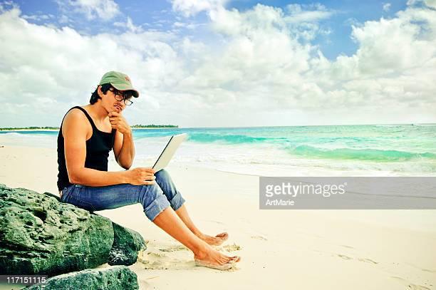 Giovane uomo con laptop a Mare