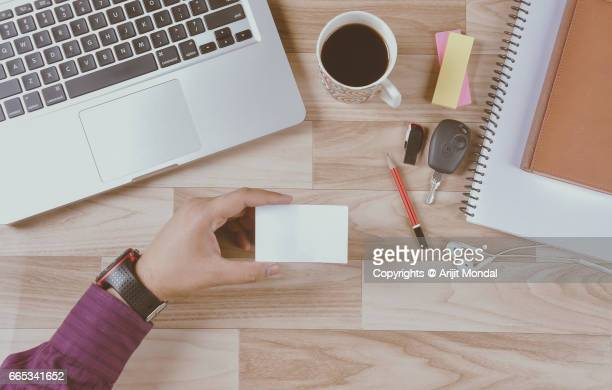 Young man with laptop holding an empty credit card top view retro style