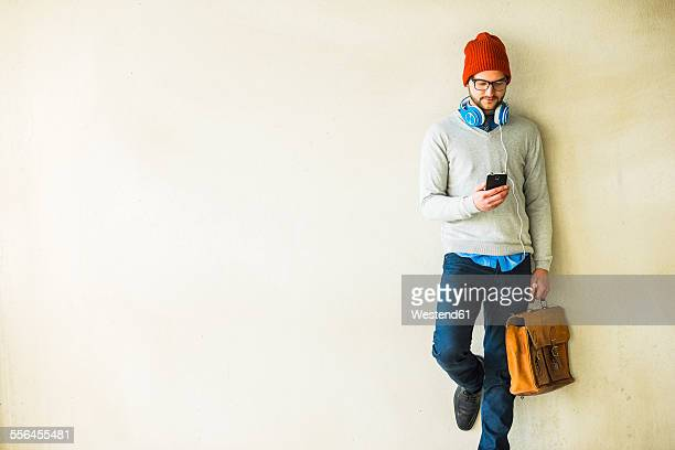 Young man with leather bag looking on cell phone