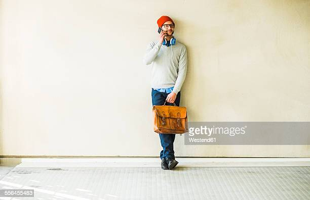 Young man with leather bag talking on cell phone