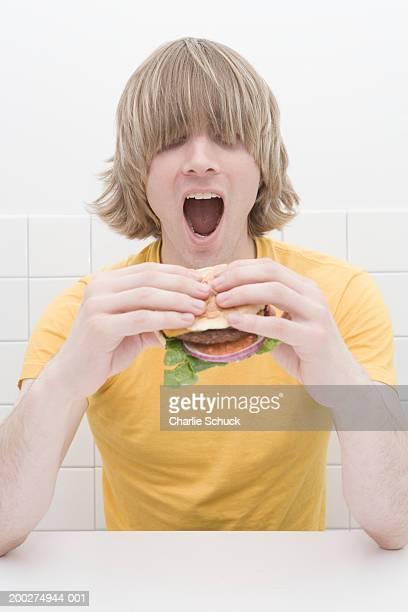 Young man with long fringe covering eyes, eating hamburger