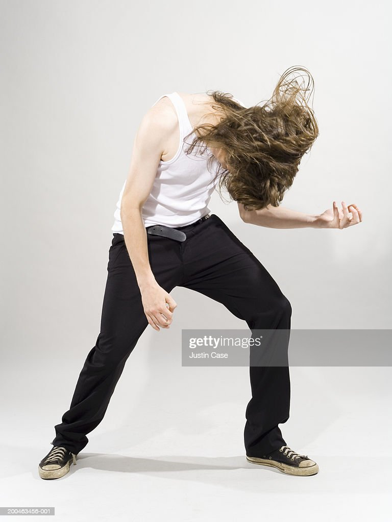 Young man with long hair head banging while playing air guitar