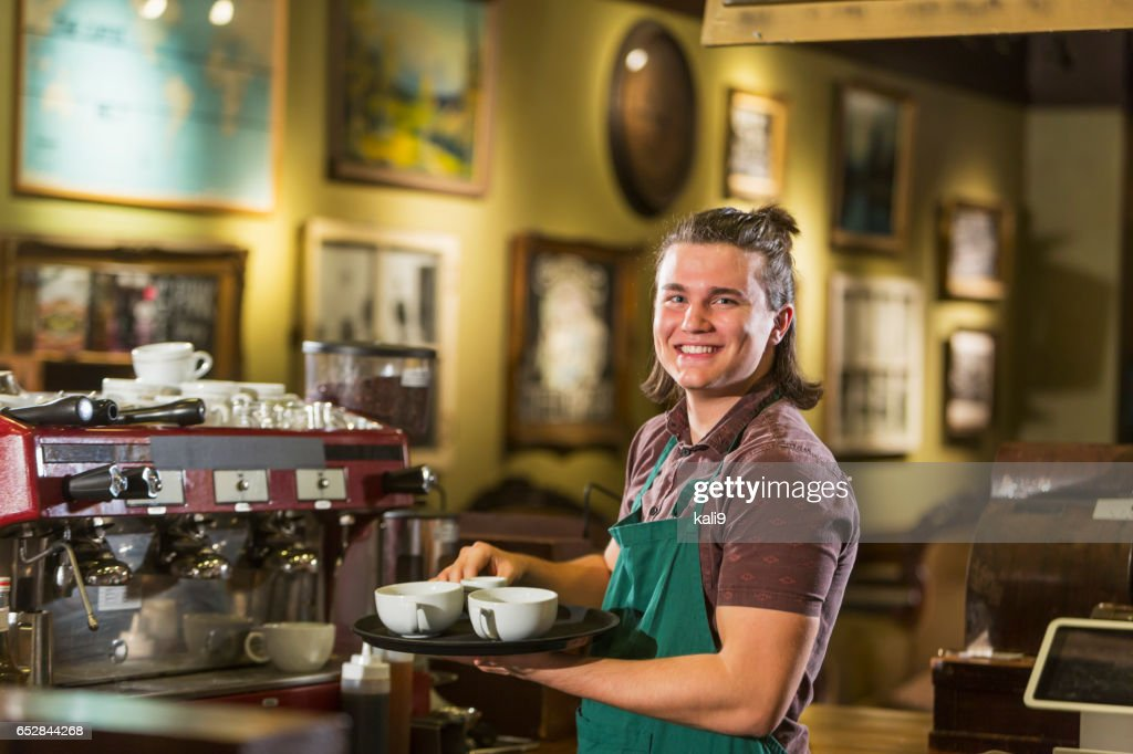 Young man with long hair working in coffee shop : Stock Photo