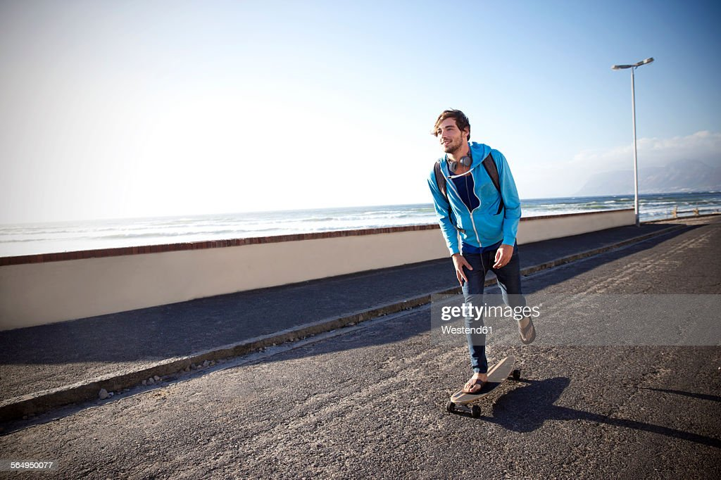 Young man with longboard on coastal road