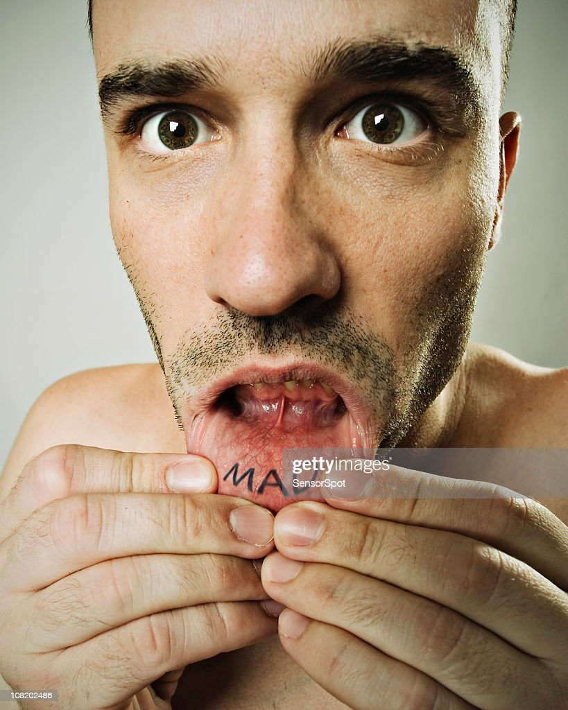 Young Man with Mad Lip Tattoo : Stock Photo