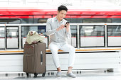 Young man with mobile phone at subway station