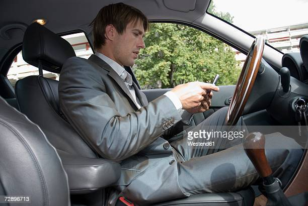 Businessman using mobile phone in car, side view, close-up