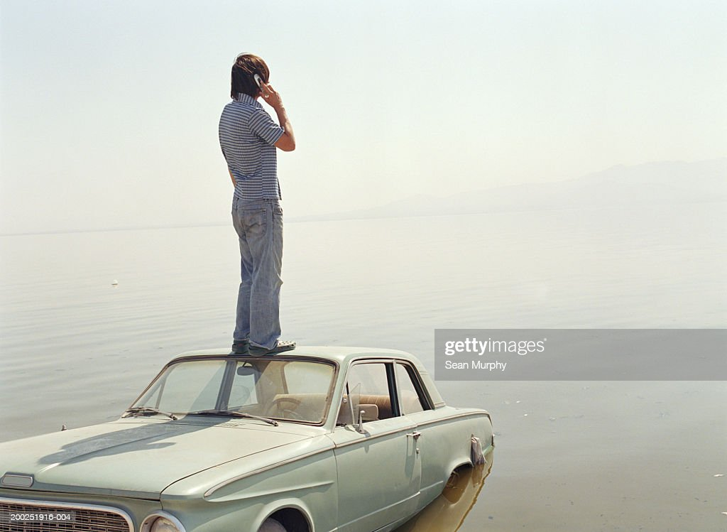 Young man with mobile phone standing on roof of car in water