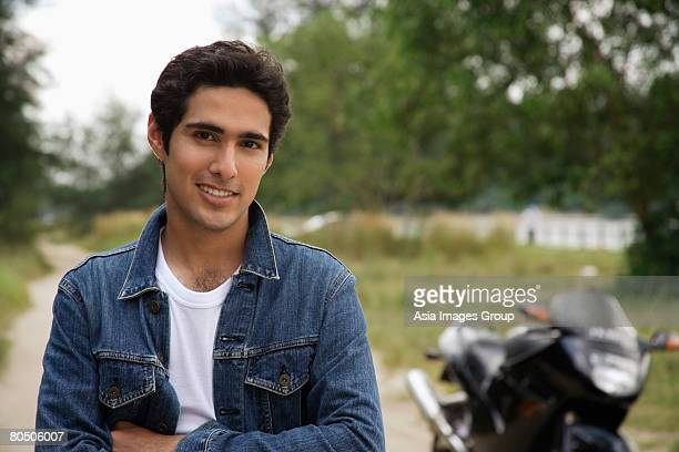 Young man with motorbike smiling at camera