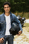 Young man with motorcycle helmet smiling at camera